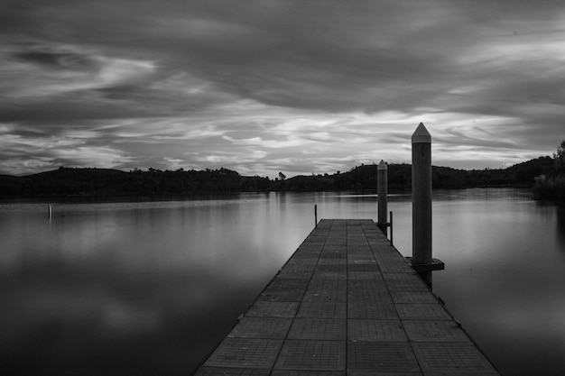 Greyscale of a pier on the sea surrounded by islands covered in greenery under a cloudy sky