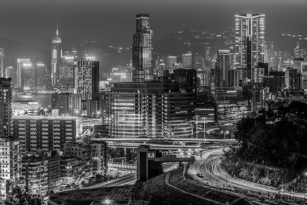 Greyscale shot of the beautiful city lights and buildings captured at night in hong kong
