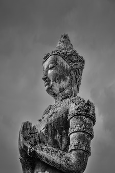 Greyscale shot of a buddha statue under the dark sky