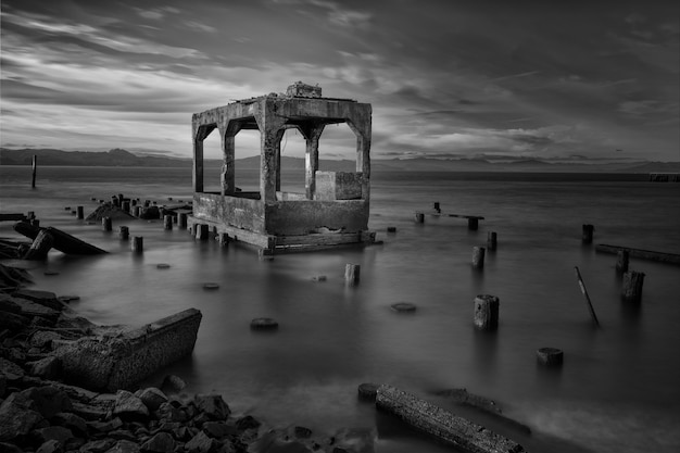 Greyscale shot of building ruins surrounded by wooden logs in the sea under the beautiful cloudy sky