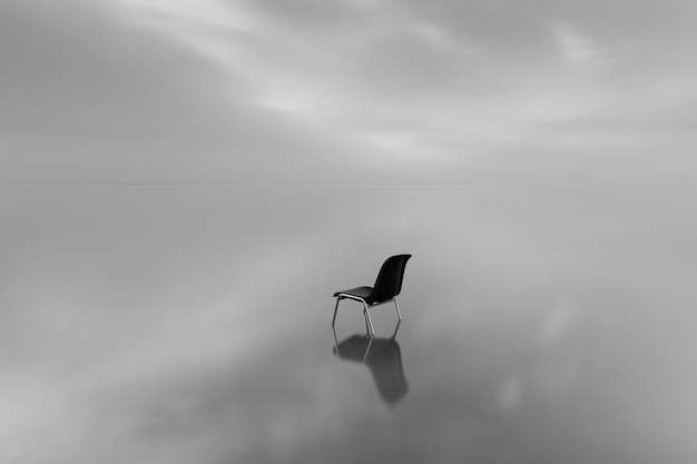 Greyscale shot of a chair on a water surface with a reflection on a rainy day