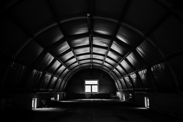 Greyscale shot of a dark tunnel room with a window