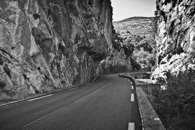 Scatto in scala di grigi di una strada vuota circondata da rocce sotto la luce del sole durante il giorno