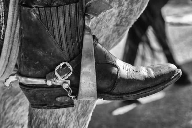 Scatto in scala di grigi dei piedi con gli stivali su una staffa di una sella