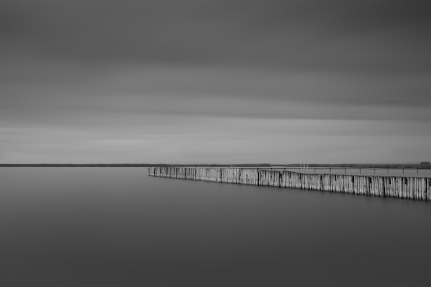 Greyscale shot of a long pier near the sea under the storm clouds