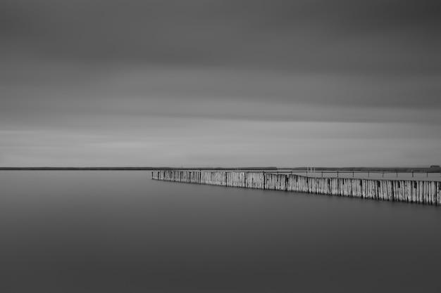 Scatto in scala di grigi di un lungo molo vicino al mare sotto le nuvole temporalesche