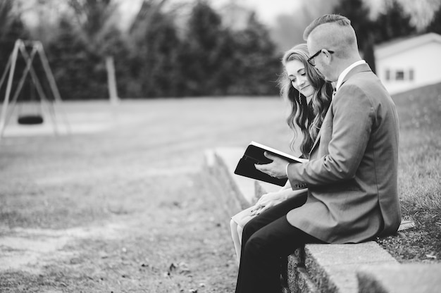 Greyscale shot of a male and a female wearing formal clothes while reading together in a garden