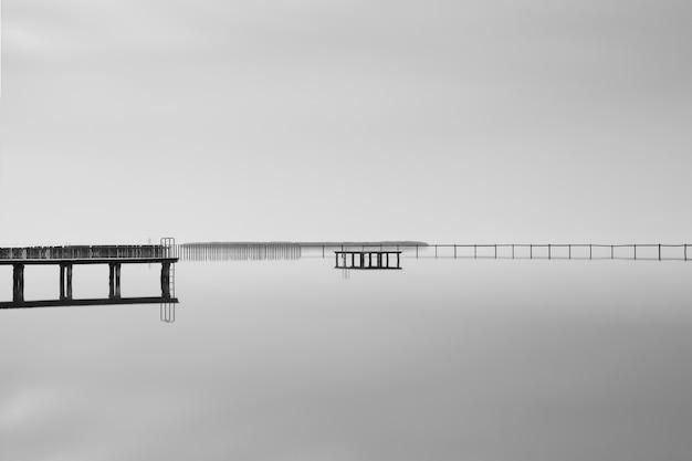 美しい曇り空の下で海の近くの木製の桟橋のグレースケールショット