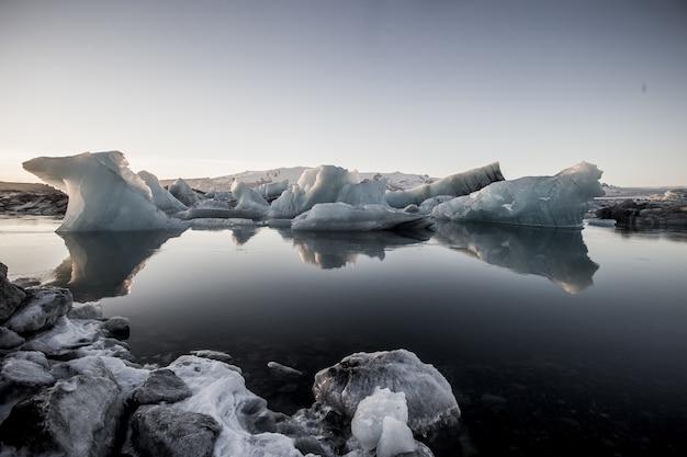 アイスランド、雪に覆われたヨークルスアゥルロゥンの凍った水の近くの氷山のグレースケールショット