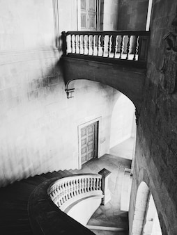 スペイン、グラナダのアルハンブラ宮殿の階段とホールのグレースケールショット