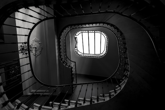 Greyscale shot of the spiral staircase of a building