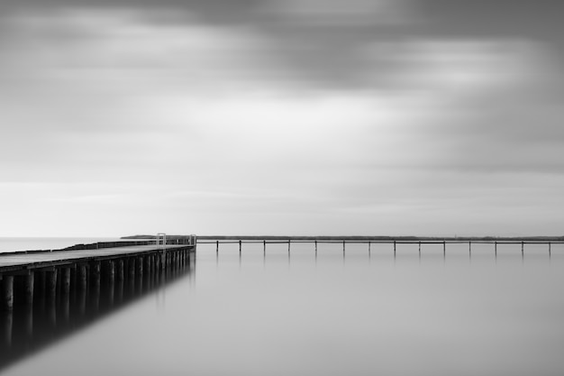 Greyscale shot of a wooden pier near the sea under the beautiful cloudy sky