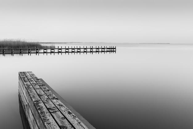 Scatto in scala di grigi di un molo in legno vicino al mare durante il giorno