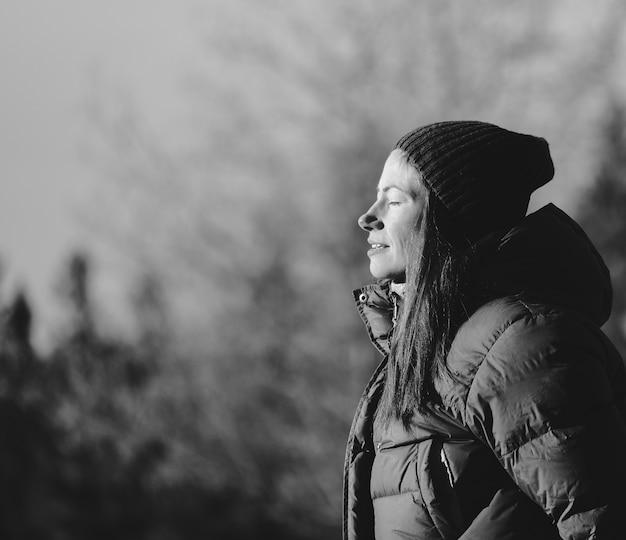 Scala di grigi del profilo laterale di una donna con un berretto circondato da alberi
