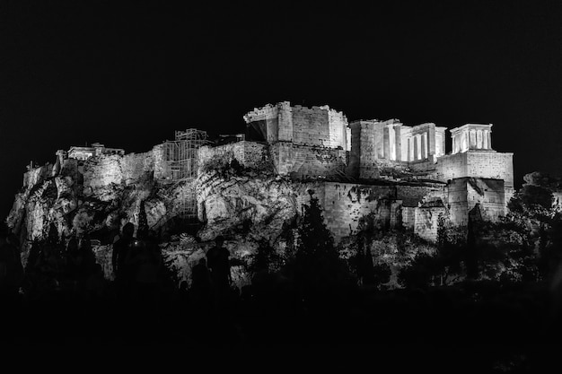 Greyscale of the temple of olympian zeus under the lights surrounded by trees during the night