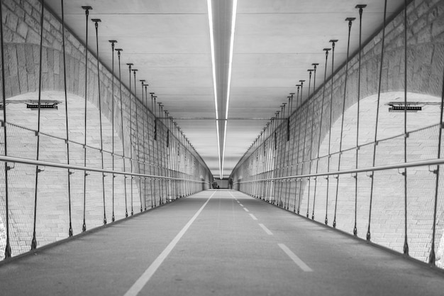 Greyscale of a tunnel surrounded by the lights during daytime