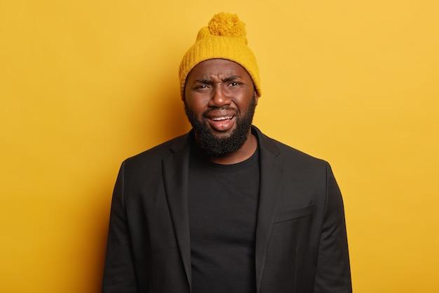 슬픔에 잠긴 흑인 힙 스터 남자는 불만으로 얼굴을 찌푸리고 노란 모자와 검은 양복을 입고 불쾌한 소식을 받고 노란색 배경에 포즈를 취합니다. 부정적인 인간의 얼굴 표현 개념