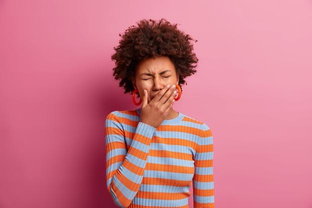 Una donna afroamericana addolorata e dispiaciuta copre gli occhi, piange per la disperazione, ha un'espressione del viso frustrata, indossa un maglione a righe casual, ha un grosso problema, è depressa per qualcosa. burnout emotivo