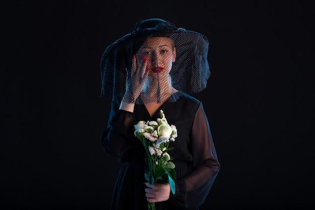 Donna in lutto vestita di nero con fiori sul nero tristezza funerale morte