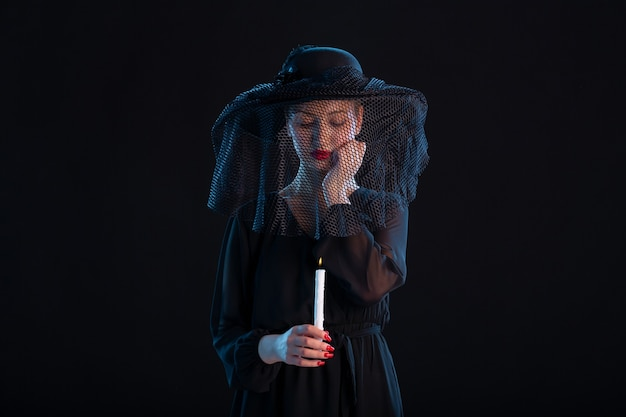 Grieving female dressed in black with burning candle on black  death funeral
