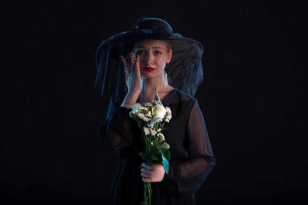 Donna in lutto vestita di nero con fiori su scrivania nera isolata morte funerale