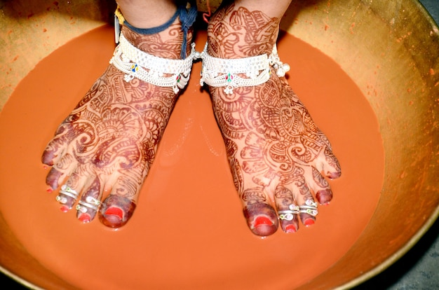 Griha pravesh ritual - right feet of a newly married indian hindu bride in saree stepping in a plate filled with liquid kumkum before entering house for the first time