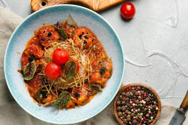 토마토 소스와 쌀을 곁들인 구운 새우는 배경에 재료가 있는 콘크리트 테이블에 접시에 닫습니다
