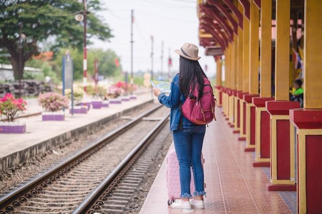 Молодое азиатское gril идя на вокзал перед перемещением.