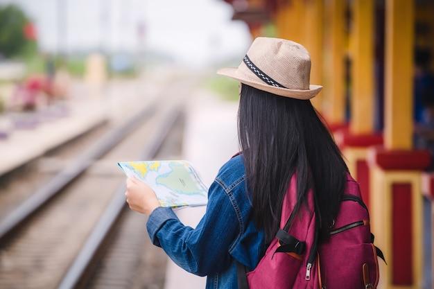 Молодое азиатское gril идя на вокзал перед перемещением. концепция работы и путешествий.