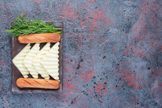 화이트 치즈 조각을 곁들인 구운 소시지.