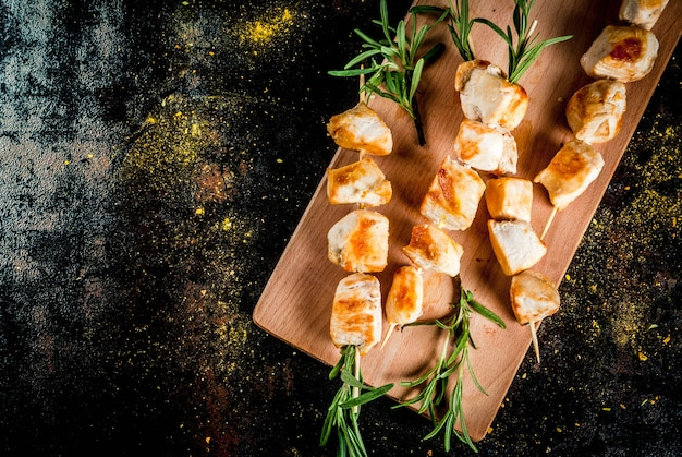 Grill, barbecue meat. chicken skewers with rosemary. on a black rusty metallic ,  top view