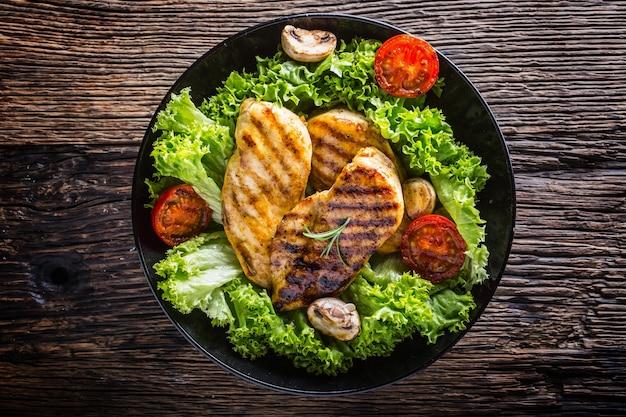 Куриная грудка гриль. жареная и запеченная на гриле куриная грудка с салатом, помидорами и грибами.