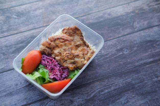 테이크 아웃 플라스틱 상자에 치킨 라이스와 샐러드를 굽습니다.