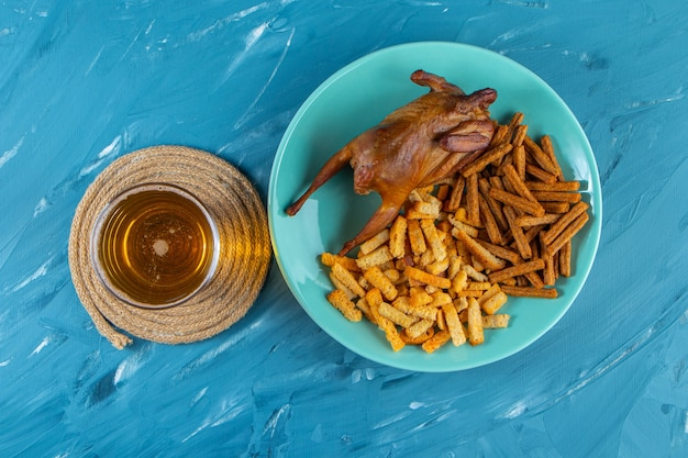 Grill and croutons on a plate next to pint, , on the blue surface.