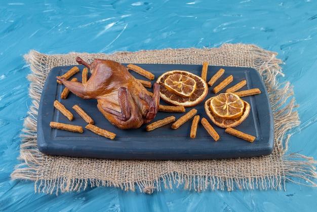 Griglia, limone essiccato e crostini su un vassoio sul tovagliolo di juta, sulla superficie blu.