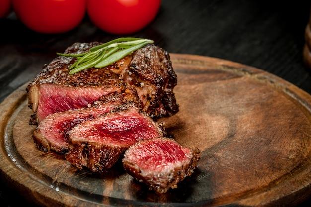 칼과 포크로 나무 판자에 소금 후추와 로즈마리를 곁들인 육즙이 풍부한 쇠고기 스테이크를 굽습니다. 정물