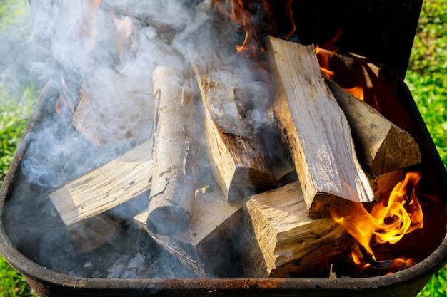 バーベキューをするために薪と煙で屋外でグリルします。
