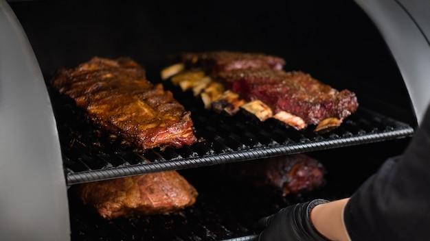 Гриль-ресторанная кухня. крупный план шеф-повара приготовления мяса птицы, говядины и свинины, ребер в курильщике барбекю.