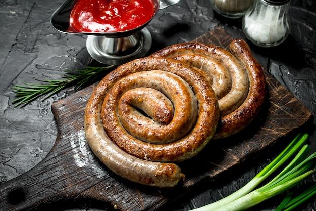 Колбаски гриль с томатным соусом и специями на деревянном столе.