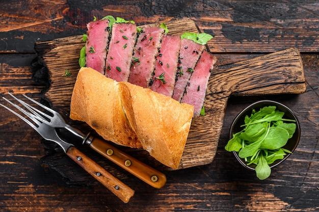 Жареный стейк из тунца ахи и сэндвич с авокадо с рукколой на разделочной доске. темный деревянный фон. вид сверху.