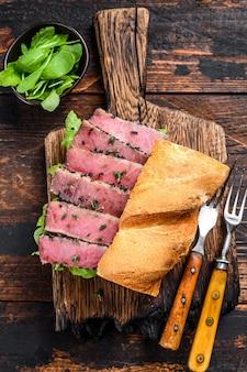 Grilled ahi tuna steak and avocado sandwich with arugula on a cutting board.
