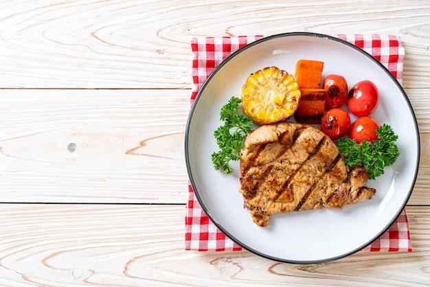 Стейк из филе свинины на гриле и барбекю с кукурузой, морковью и помидорами