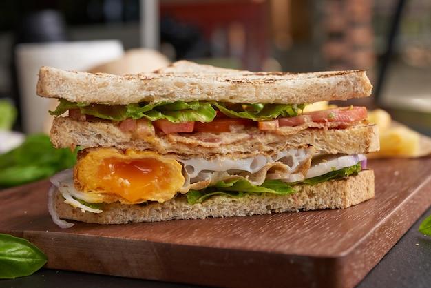 Жареный и бутерброд с беконом, жареным яйцом, помидорами и салатом на деревянной разделочной доске