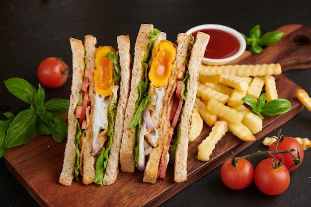 ベーコン、揚げ卵、トマト、レタスのグリルとサンドイッチを木製のまな板でお召し上がりいただけます