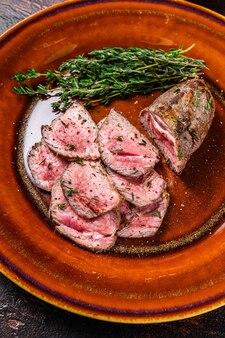 접시에 구운 및 얇게 썬 양고기 등심 고기 스테이크. 어두운 배경입니다. 평면도.