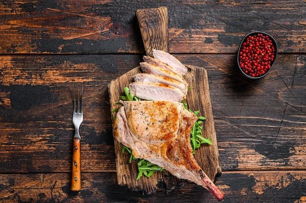 Жареный и нарезанный мясной стейк из свиной отбивной томагавк на мраморной доске