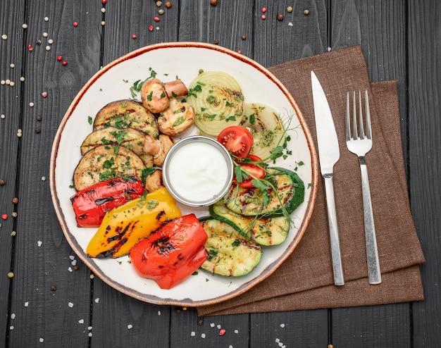 접시에 마늘 소스와 함께 구운 모듬 야채