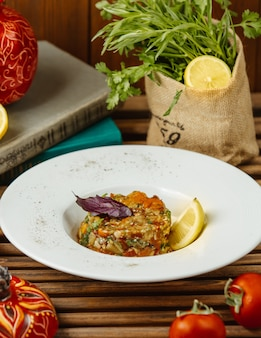 Grilled aubergine salad served with lemon slice