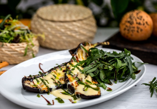 Grilled aubergine slices garnished with melted cheese and tarragon