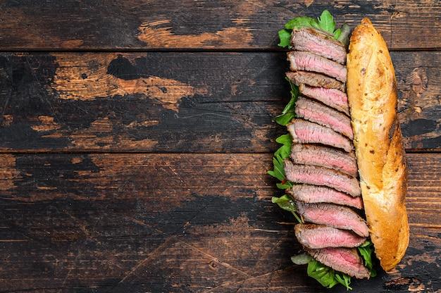 Сэндвич из багета со стейком на гриле с рукколой и сыром